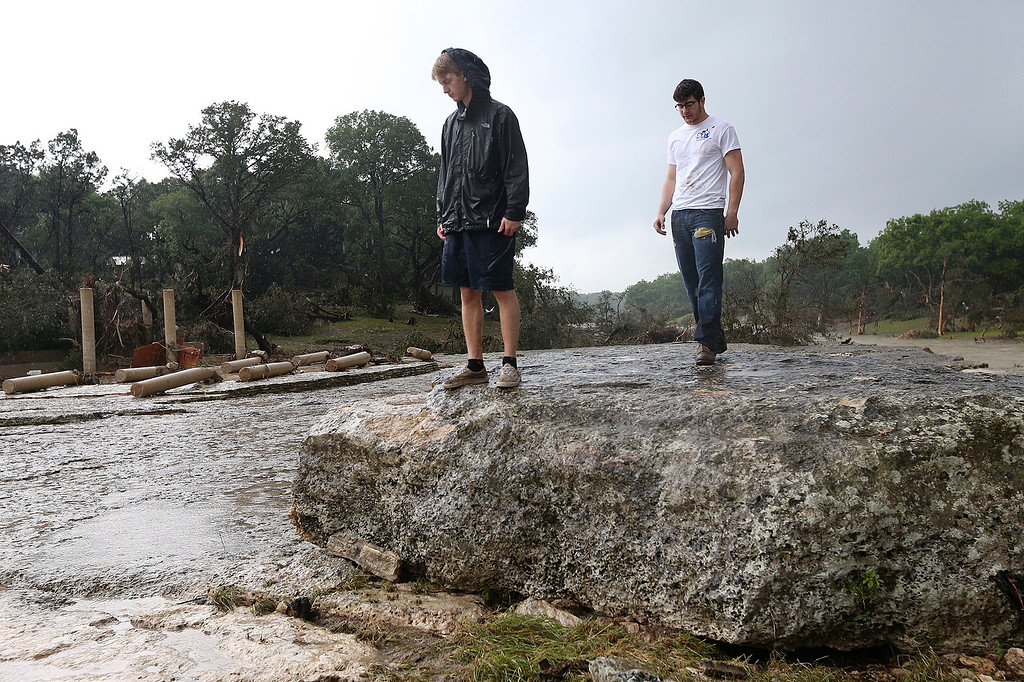 . Grant Guzal, left, and Hudson Doty stand near the remains a house, Monday, May 25, 2015, in Wimberley, Texas. Jonathan McComb and his family were guests in the house when it was swept away by floodwaters. McComb escaped but his family is missing. Several people were reported missing in flash flooding from a line of storms that stretched from the Gulf of Mexico to the Great Lakes. (Jerry Lara/The San Antonio Express-News via AP)