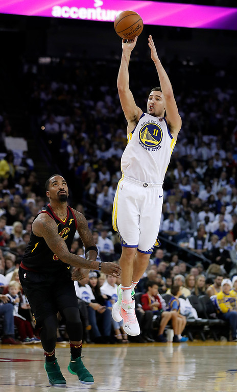 . Golden State Warriors guard Klay Thompson (11) shoots over Cleveland Cavaliers guard JR Smith (5) during the second half of an NBA basketball game in Oakland, Calif., Monday, Dec. 25, 2017. The Warriors won 99-92. (AP Photo/Tony Avelar)