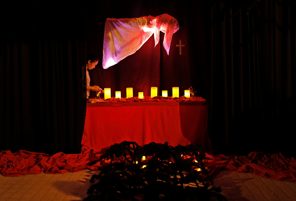 . A woman lights candles amid decorations on Halloween night in Hong Kong, Thursday, Oct. 31, 2013. (AP Photo/Vincent Yu)