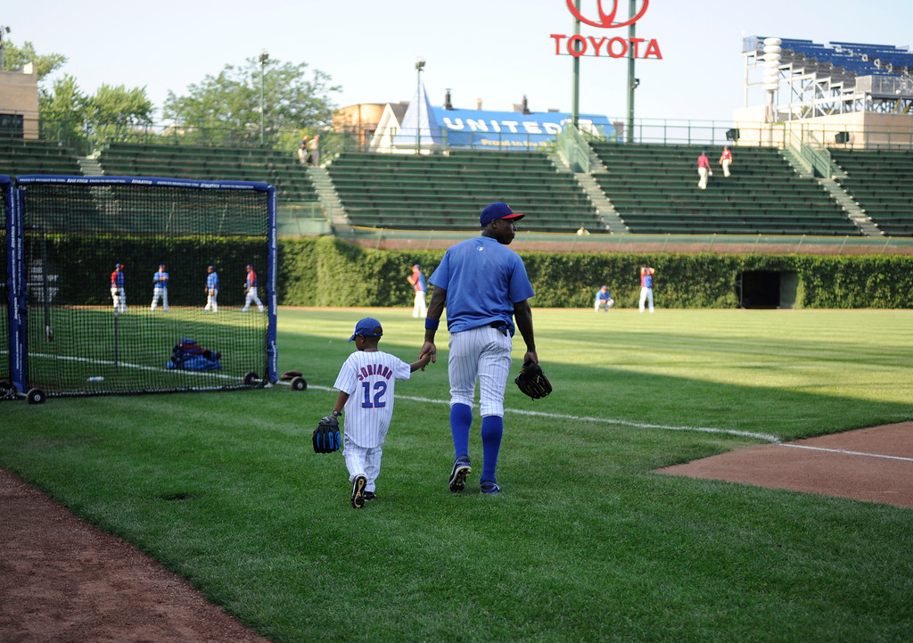 . CHICAGO, IL - JULY 10: Alfonso Soriano #12 of the Chicago Cubs walks to the outfield with his son during batting practice before the game between the Chicago Cubs and the Los Angeles Angels of Anaheim on July 10, 2013 at Wrigley Field in Chicago, Illinois. (Photo by David Banks/Getty Images)