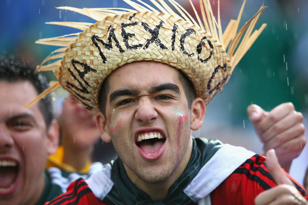 . A Mexico fan cheers in the rain during the 2014 FIFA World Cup Brazil Group A match between Mexico and Cameroon at Estadio das Dunas on June 13, 2014 in Natal, Brazil.  (Photo by Julian Finney/Getty Images)