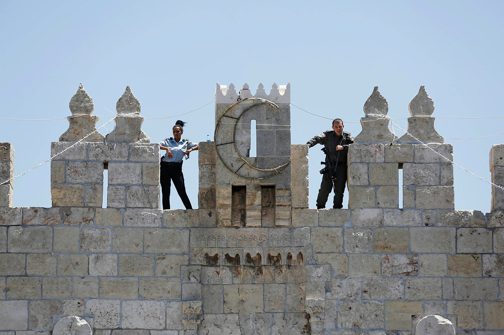. Israeli police officers stand guard atop a wall overlooking Damascus Gate in Jerusalem\'s Old City, during the holy month of Ramadan July 26, 2013. REUTERS/Baz Ratner