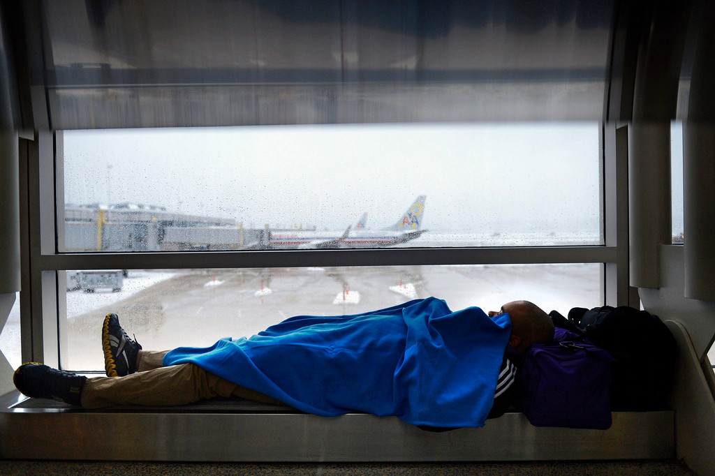 . A passenger kills time with a nap as work crews continue to clear snow from the runways at Reagan National Airport in Arlington, Virginia, USA, 13 February 2014. All flights from Reagan National were grounded as the Washington, DC metropolitan area received over a foot of snow. Heavy winter snowfalls hit large parts of USA from Texas to the East Coast.  EPA/SHAWN THEW