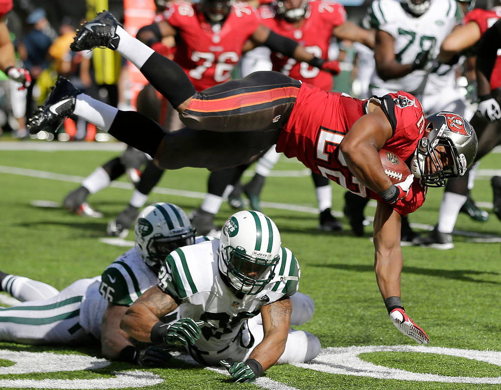 . Tampa Bay Buccaneers running back Doug Martin (22) flies after being hit by New York Jets outside linebacker DeMario Davis (56) and strong safety Dawan Landry (26) in the second half of an NFL football game, Sunday, Sept. 8, 2013, in East Rutherford, N.J. (AP Photo/Mel Evans)