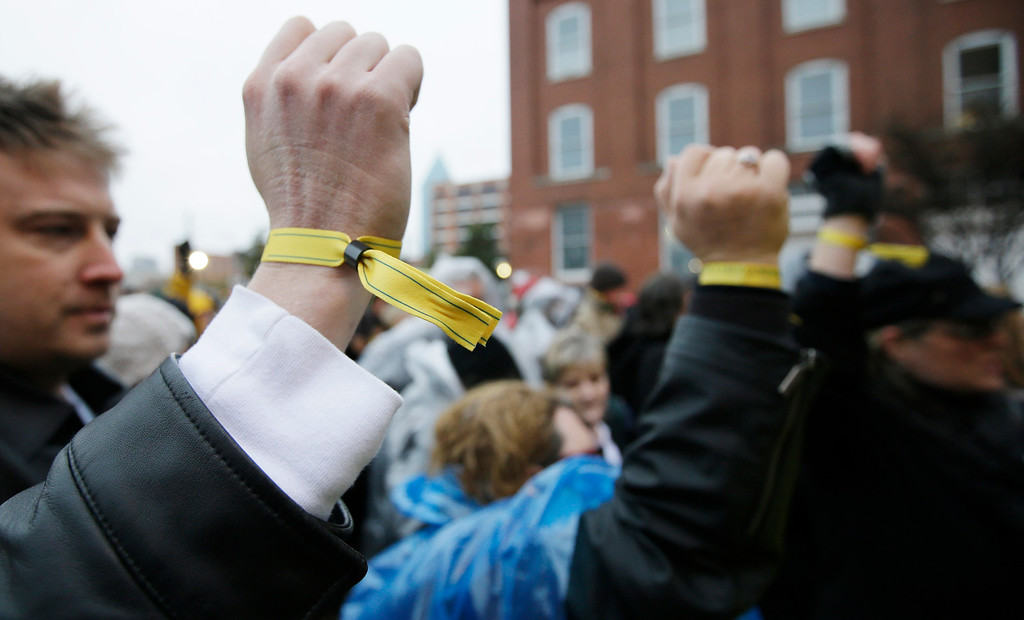 . Sean MacLean of Calgary, Alberta, Canada, left, and Colleen Bonner of Hurst, Texas display yellow wrist bands for access before ceremony to mark the 50th anniversary of the assassination of John F. Kennedy, Friday, Nov. 22, 2013, at Dealey Plaza in Dallas. President Kennedy\'s motorcade was passing through Dealey Plaza when shots rang out on Nov. 22, 1963. (AP Photo/Tony Gutierrez)