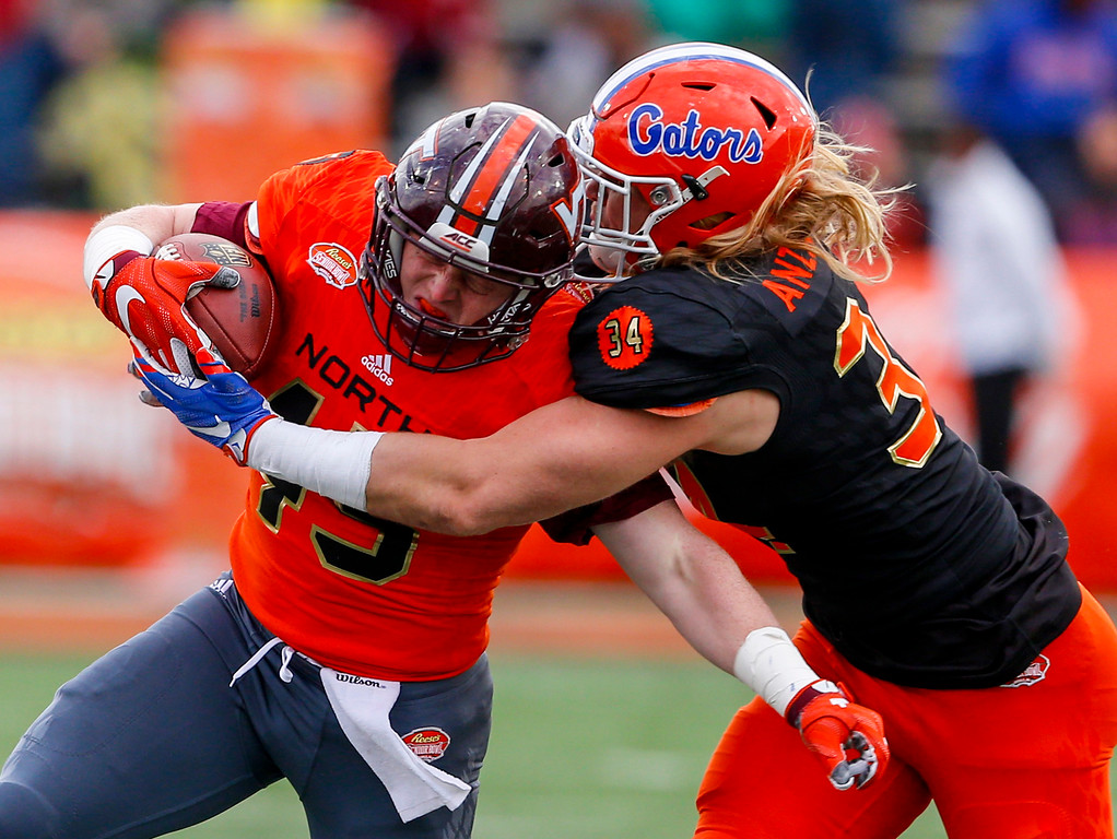 . North squad fullback Sam Rogers of Virginia Tech (45) is tackled by South squad inside linebacker Alex Anzalone of Florida (34) as he carries the ball during the second half of the Senior Bowl NCAA college football game, Saturday, Jan. 28, 2017, at Ladd-Peebles Stadium in Mobile, Ala. (AP Photo/Butch Dill)