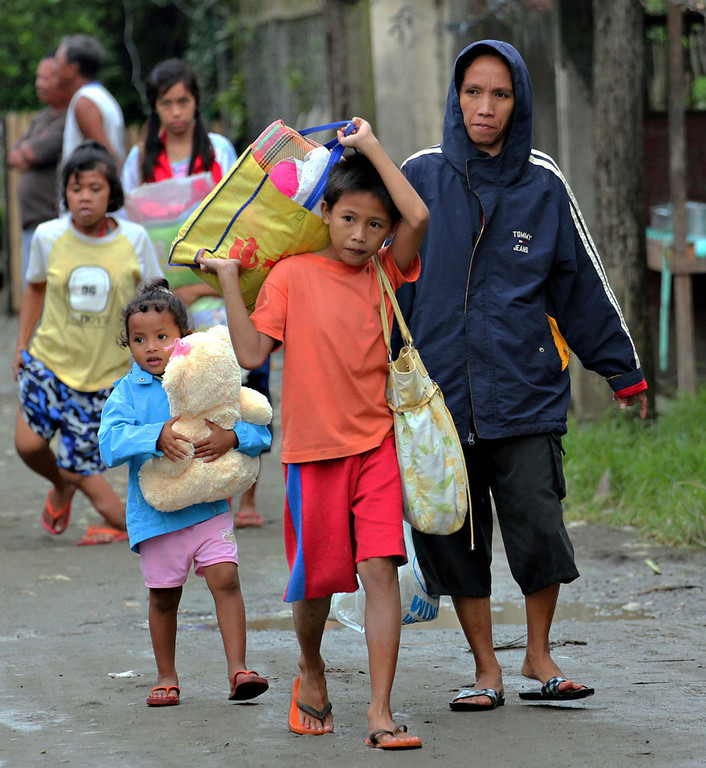 . Residents evacuate to safer grounds in anticipation of Typhoon Bopha in Butuan city in southeastern Philippines Tuesday, Dec. 4, 2012. Typhoon Bopha, one of the strongest typhoons to hit the Philippines this year, barreled across the country\'s south on Tuesday, killing dozens of people and forcing more than 50,000 to flee from inundated villages. (AP Photo/Erwin Mascarinas)
