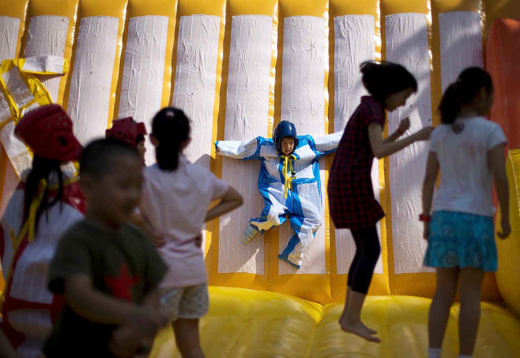 . A child plays on a sticky wall as others jump on an inflatable balloon bouncer on International Children\'s Day organized by the Chinese Foreign Affairs Office at Children\'s Palace of Dongcheng district in Beijing Saturday, June 1, 2013. (AP Photo/Andy Wong)