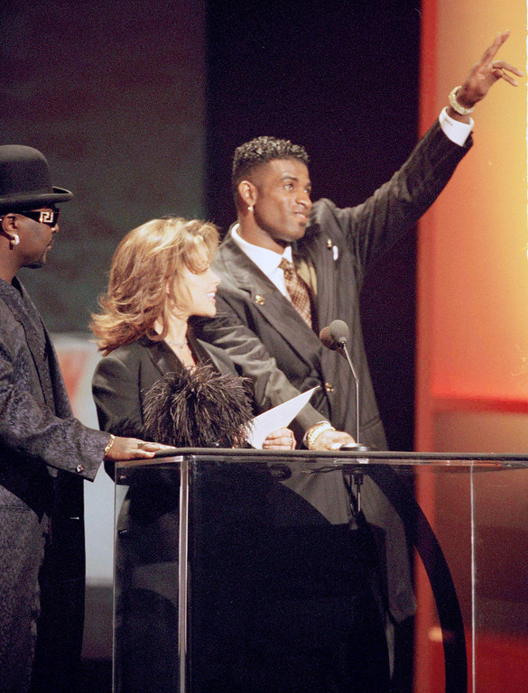 . San Francisco 49ers star Deion Sanders, fresh from his team\'s Super Bowl victory over the San Diego Chargers, acknowledges cheers, and a few catcalls, from the crowd as he and Paula Abdul prepare to present the award for favorite male pop/rock artist at the 22nd annual American Music Awards, Jan. 30, 1995, in Los Angeles. (AP Photo/Reed Saxon)