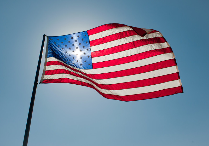 Cross shaped flare, shining through the American Flag at a Memorial Day display in Benton, Ks.
