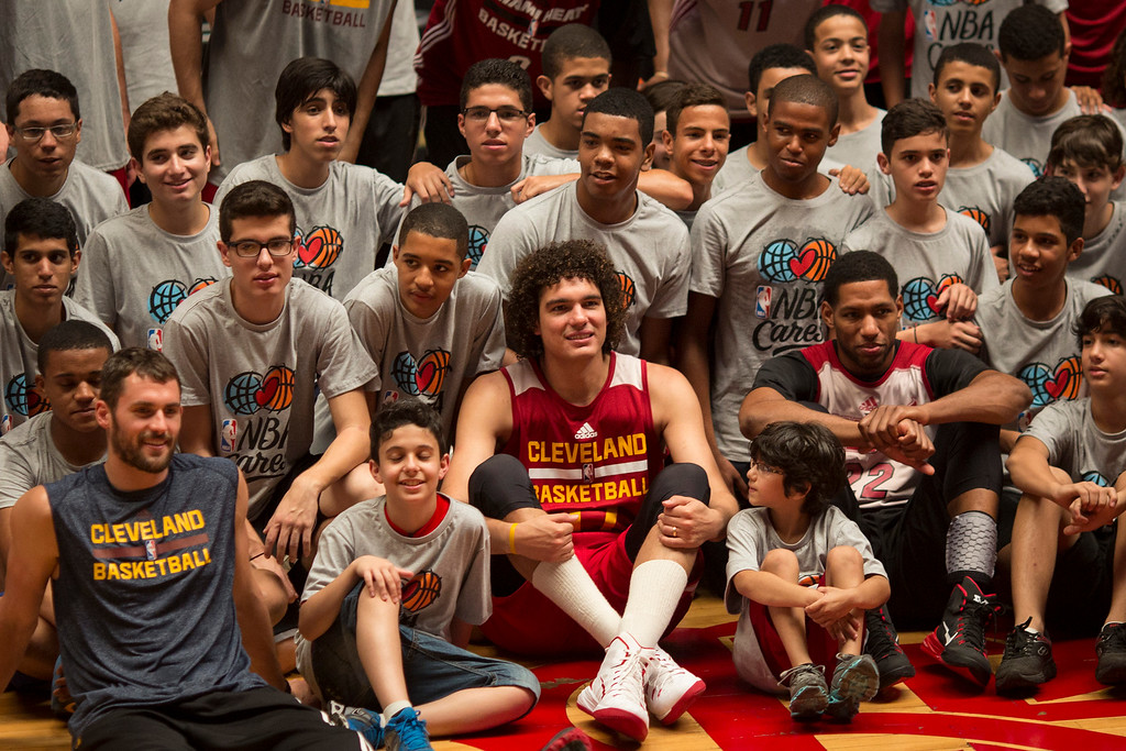 . The Cleveland Cavaliers\' Anderson Varejao, center, poses for photos with kids before the start of a training session in Rio de Janeiro, Brazil, Thursday, Oct. 9, 2014. The Cleveland Cavaliers will play the Miami Heat in a preseason game in Rio, on Saturday, as part of the NBA Global Games. (AP Photo/Felipe Dana)