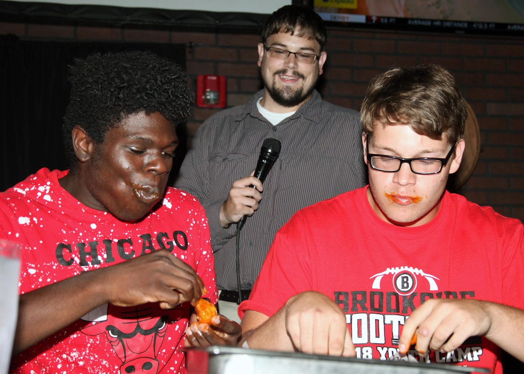 . Brookside\'s Malachi Sheffield and Tim Borgmann pause during the second round of the wing eating contest on Tuesday.