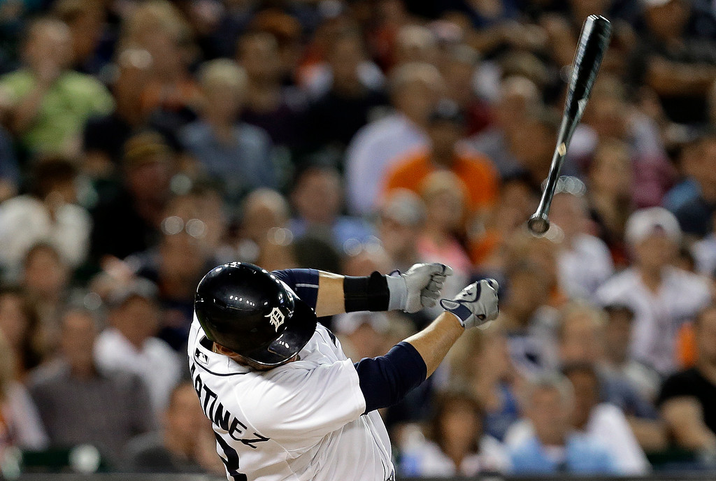 . Detroit Tigers\' J.D. Martinez loses his bat which landed in the stands on a pop out against the Los Angeles Dodgers in the seventh inning of a baseball game in Detroit, Tuesday, July 8, 2014. (AP Photo/Paul Sancya)