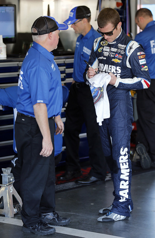 . DAYTONA BEACH, FL - FEBRUARY 20:  Kasey Kahne (R), driver of the #5 Farmers Insurance Chevrolet, signs his autograph in the garage during practice for the NASCAR Sprint Cup Series Daytona 500 at Daytona International Speedway on February 20, 2013 in Daytona Beach, Florida.  (Photo by Sam Greenwood/Getty Images)