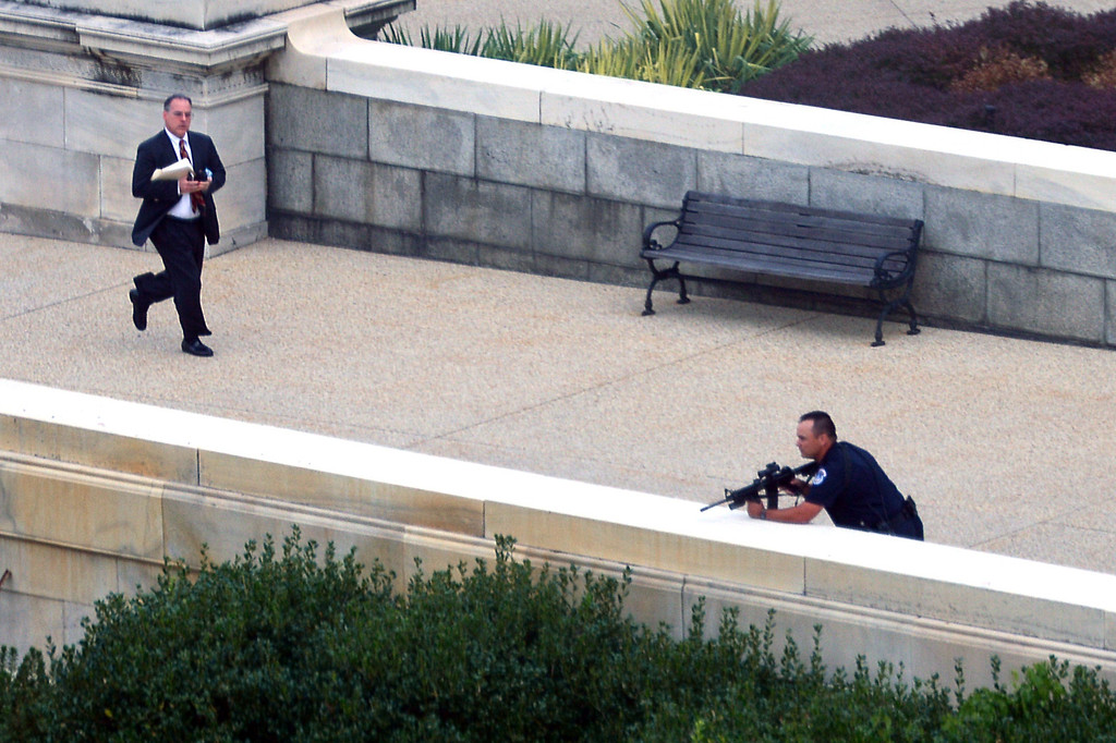 """. A man runs for cover as a police officer takes a shooting position at the site of a shooting October 3, 2013 on Capitol Hill in Washington, DC. The US Capitol was placed on security lockdown Thursday after shots were fired outside the complex, senators said. \""""Shots fired outside the Capitol. We are in temporary lock down,\"""" Senator Claire McCaskill said on Twitter. Police were seen running within the Capitol building and outside as vehicles swarmed to the scene. AFP PHOTO / Mandel NGAN/AFP/Getty Images"""