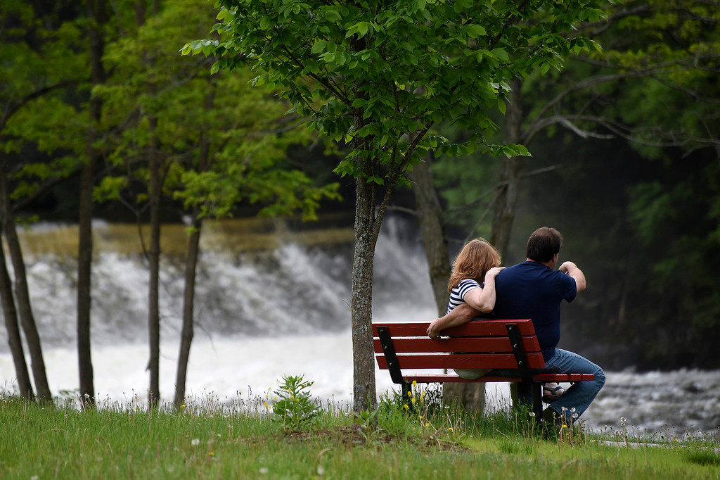 . Kayla Rice/Reformer A couple sits on a bench overlooking the Ashuelot River Dam on Memorial Day before the town\'s parade.