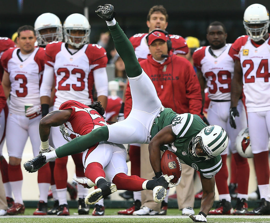 . Stephen Hill #84 of the New York Jets is hit by Greg Toler #28 of the Arizona Cardinals on December 2, 2012 at MetLife Stadium in East Rutherford, New Jersey. The New York Jets defeated the Arizona Cardinals 7-6.(Photo by Elsa/Getty Images)