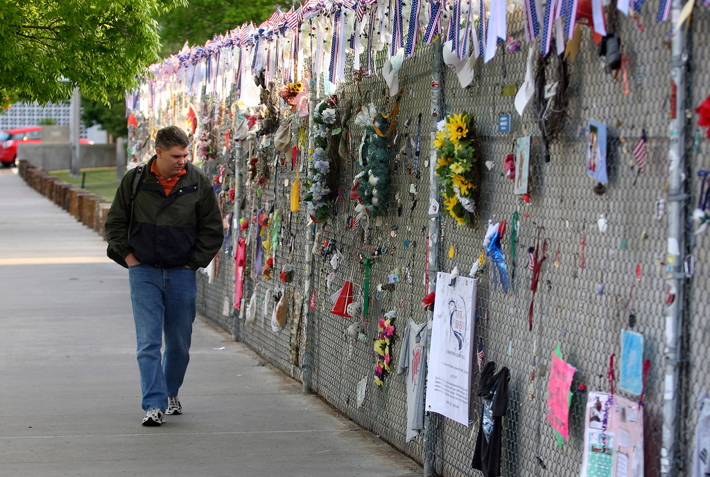 . Oklahoma City resident Kevin Fruendt walks past the west fence where dedications are hung to the victims of the Murrah Building bombing during the 15th anniversary observance ceremony of the Murrah Building bombing April 19, 2010 in Oklahoma City, Oklahoma. Timothy McVeigh detonated a bomb outside the Alfred P. Murrah Federal Building on April 19, 1995, killing 168 people in what was then the largest terrorist attack in United States history. (Photo by Brett Deering/Getty Images)