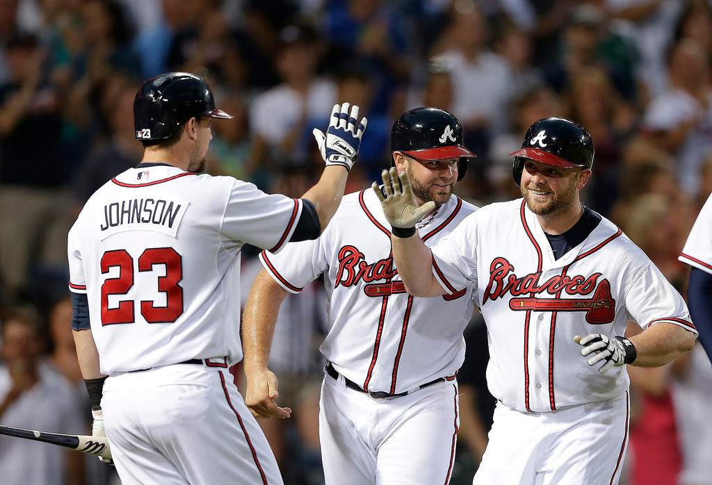. Atlanta Braves\' Brian McCann, right, celebrates with Evan Gattis and Chris Johnson (23) after hitting a three-run home run in the fourth inning of a baseball game against the Colorado Rockies in Atlanta, Tuesday, July 30, 2013. (AP Photo/John Bazemore)