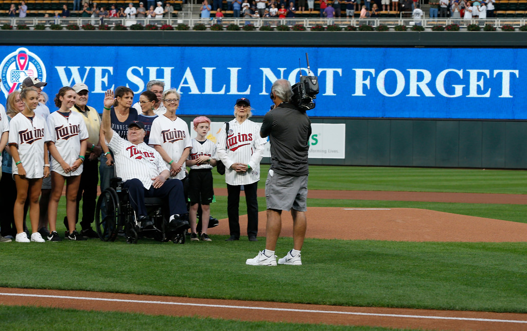 . Tom Barnett Sr., in wheelchair, waves as the family was recognized during a tribute to 9/11 prior to a baseball game between the Minnesota Twins and the New York Yankees, Tuesday, Sept. 11, 2018, in Minneapolis. Tom Barnett Jr. was aboard Flight 93 which went down in Pennsylvania. (AP Photo/Jim Mone)