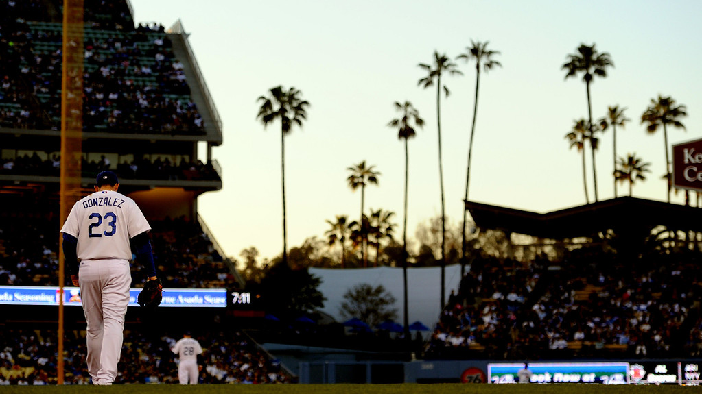 . Los Angeles Dodgers first baseman Adrian Gonzalez walks to his position as the sunsets in the second inning of their baseball game on Wednesday, April 17, 2013 in Los Angeles.   (Keith Birmingham/Pasadena Star-News)