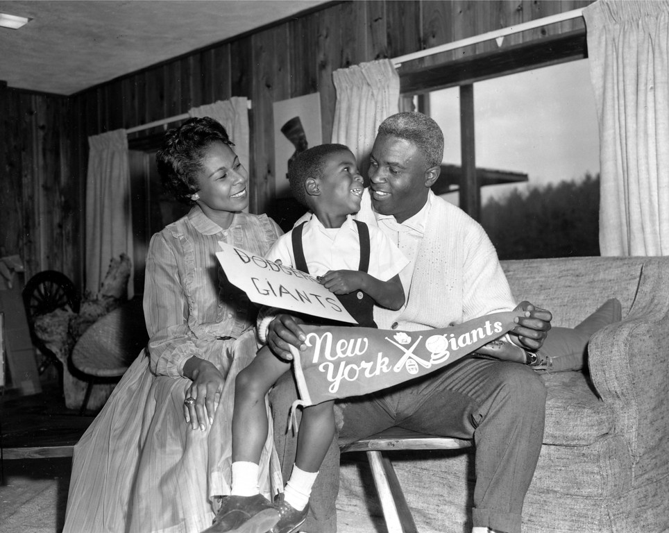 . Jackie Robinson, Brooklyn Dodgers star since breaking into Major League baseball in 1947, is shown with his wife, Rachel, and their four-year-old son, Jackie Jr., in their home in Stamford, Conn., Dec. 13, 1956.    (AP Photo/John Lindsay)