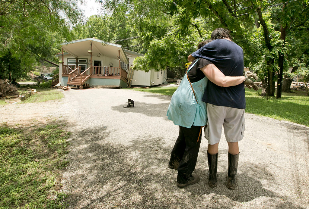 . Michelle Johnson, left, hugs neighbor John Meadows on Roundup Drive in Wimberley, Texas, on Tuesday, May 26, 2015. Several homes on the street were heavily damaged or destroyed, including theirs, by the flood on Blanco River. (Jay Janner/Austin American-Statesman via AP)