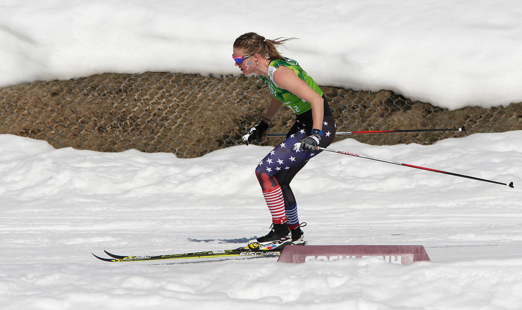 . Sadie Bjornsen of the United States skis in a sleeveless top past a hole in the snow during the women\'s 4x5K cross-country relay at the 2014 Winter Olympics, Saturday, Feb. 15, 2014, in Krasnaya Polyana, Russia. (AP Photo/Matthias Schrader)