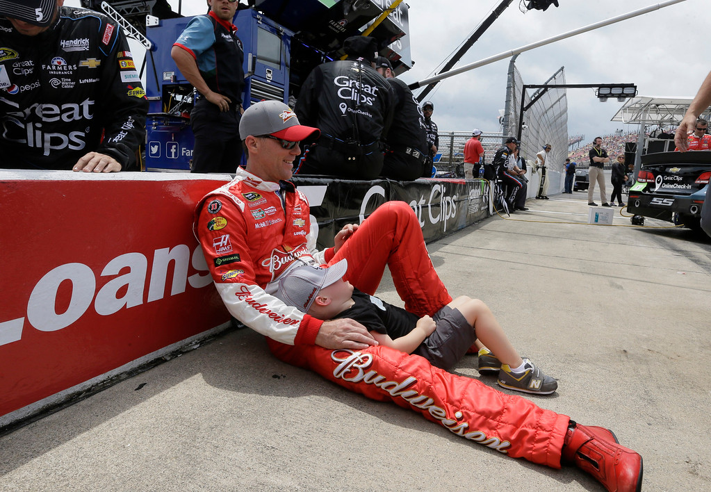 . Kevin Harvick rests against the pit row wall with his son Keelan Harvick before the NASCAR Sprint Cup series auto race at Michigan International Speedway, Sunday, June 14, 2015, in Brooklyn, Mich. (AP Photo/Carlos Osorio)