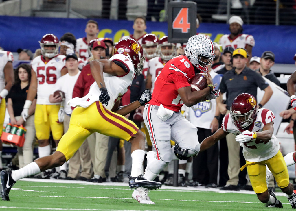 . Ohio State quarterback J.T. Barrett (16) rushes for a first down against Southern California safety Marvell Tell III (7) and cornerback Isaiah Langley (24) during the first half of the Cotton Bowl NCAA college football game in Arlington, Texas, Friday, Dec. 29, 2017. (AP Photo/LM Otero)