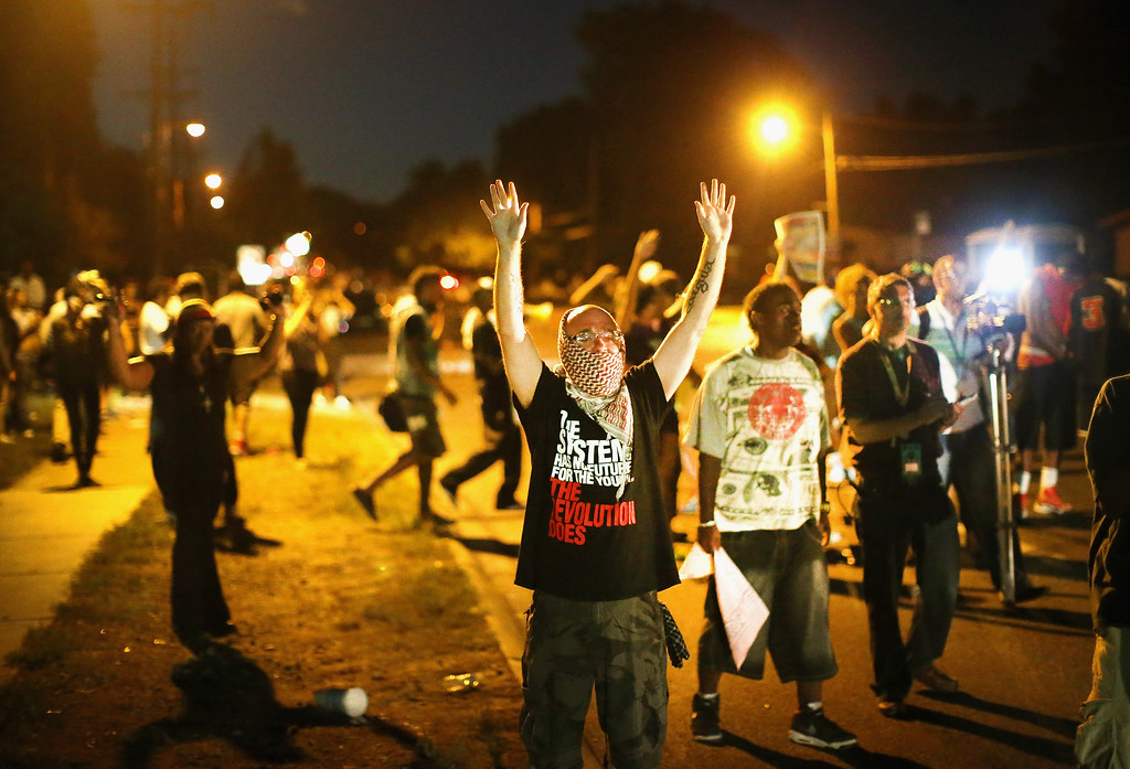 . Demonstrators protest the shooting death of teenager Michael Brown on August 13, 2014 in Ferguson, Missouri. Brown was shot and killed by a Ferguson police officer on Saturday. Ferguson, a St. Louis suburb, is experiencing its fourth day of violent protests since the killing.  (Photo by Scott Olson/Getty Images)