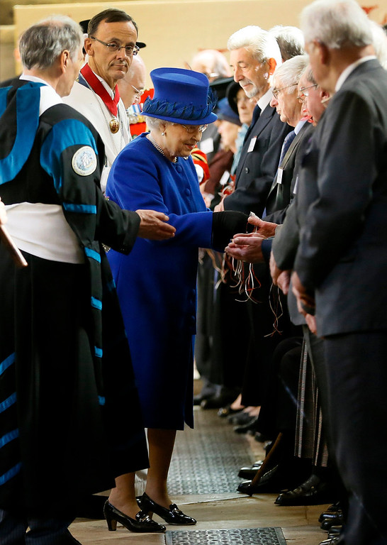 . Britain\'s Queen Elizabeth II, centre, distributes Maundy money during the Maundy service,  at Christ Church Cathedral in Oxford, England,  Thursday, March 28, 2013. The Queen distributed the Maundy money to 87 women and 87 men, one for each of The Queenís 87 years. Each recipient receives two purses, one red and one white. The red purse will contain a 5 pound coin and 50 pence coin commemorating the 60th anniversary of The Queenís Coronation. The white purse will contain uniquely minted Maundy Money. This takes the form of silver one, two, three and four penny pieces, the sum of which equals the number of years the Monarch has years of age. This year there will be 87 pennies worth distributed. (AP Photo/Kirsty Wigglesworth, Pool)