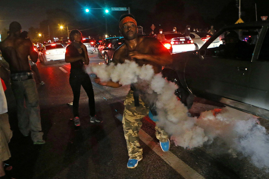 . A protester tries to throw tear gas back at the police in Ferguson, Mo., Sunday, Aug. 17, 2014. Protests over the killing of 18-year-old Michael Brown by a white police officer have entered their second week. (AP Photo/St. Louis Post-Dispatch, J.B. Forbes)