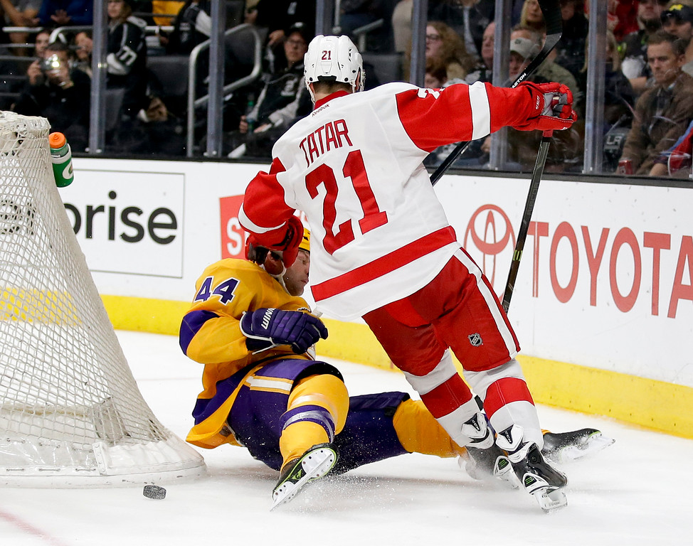 . Detroit Red Wings left wing Tomas Tatar, right, knocks Los Angeles Kings defenseman Robyn Regehr off the puck during the third period of an NHL hockey game in Los Angeles, Tuesday, Feb. 24, 2015. The Kings won 1-0. (AP Photo/Chris Carlson)