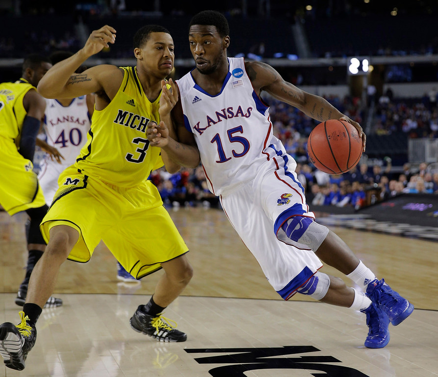 . Kansas\' Elijah Johnson (15) tries to drive past Michigan\'s Trey Burke during the first half of a regional semifinal game in the NCAA college basketball tournament, Friday, March 29, 2013, in Arlington, Texas. (AP Photo/David J. Phillip)