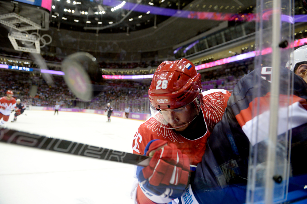 . The puck flies as Vyacheslav Voinov (26) of the Russia checks Zach Parise (9) of the U.S.A. into the boards during the first period of men\'s hockey action at Bolshoy arena. Sochi 2014 Winter Olympics on Saturday, February 15, 2014. (Photo by AAron Ontiveroz/The Denver Post)