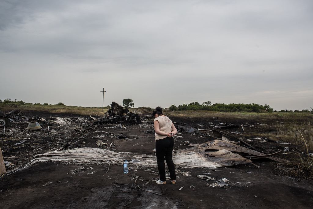 . A woman looks at the wreckage of passenger plane Air Malaysia flight MH17 on July 18, 2014 in Grabovka, Ukraine. Air Malaysia flight MH17 traveling from Amsterdam to Kuala Lumpur crashed yesterday on the Ukraine/Russia border near the town of Shaktersk. The Boeing 777 was carrying 298 people including crew members, the majority of the passengers being Dutch nationals, believed to be at least 173, 44 Malaysians, 27 Australians, 12 Indonesians and 9 Britons. (Photo by Brendan Hoffman/Getty Images)