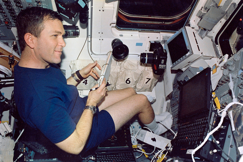 """. In this Jan. 2003 file photo, astronaut Rick D. Husband, mission commander of the space shuttle Columbia, is pictured on the aft flight deck.  Husband and six crew members were lost when Columbia broke up during re-entry over north Texas on Feb. 1, 2003, . This picture was on a roll of unprocessed film recovered by searchers from the debris later, released by NASA on June 24, 2003.  Ten years later, reminders of Columbia are everywhere, including up in the sky.  Everything from asteroids, lunar craters and Martian hills, to schools, parks, streets and even an airport (Rick Husband Amarillo International Airport) bear the Columbia astronauts\' names. Two years ago, a museum opened in Hemphill, Texas, where much of the Columbia wreckage rained down, dedicated to \""""remembering Columbia.\""""  About 84,000 pounds of that wreckage, representing 40 percent of NASA\'s oldest space shuttle, are stored at Kennedy and loaned for engineering research. (AP Photo/NASA)"""