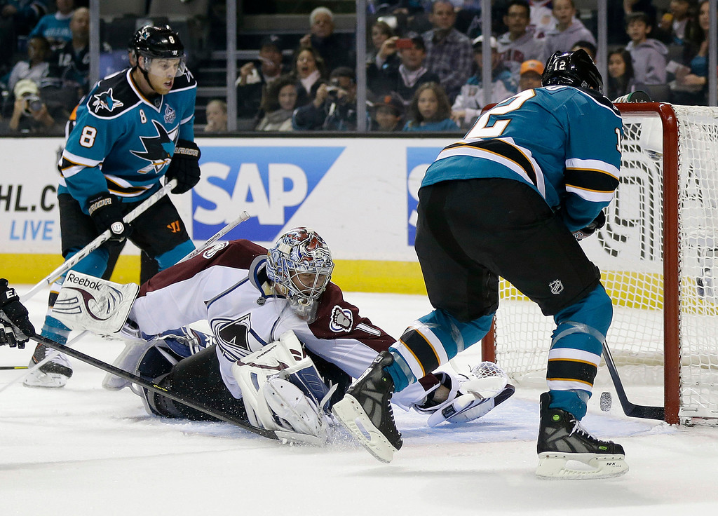 . San Jose Sharks center Patrick Marleau, right, scores past Colorado Avalanche goalie Semyon Varlamov, center, of Russia, for his second goal of the first period of an NHL hockey game in San Jose, Calif., Saturday, Jan. 26, 2013. (AP Photo/Marcio Jose Sanchez)