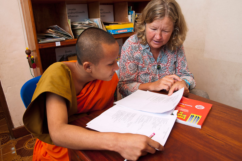 Volunteer helps Buddhist monk with English.