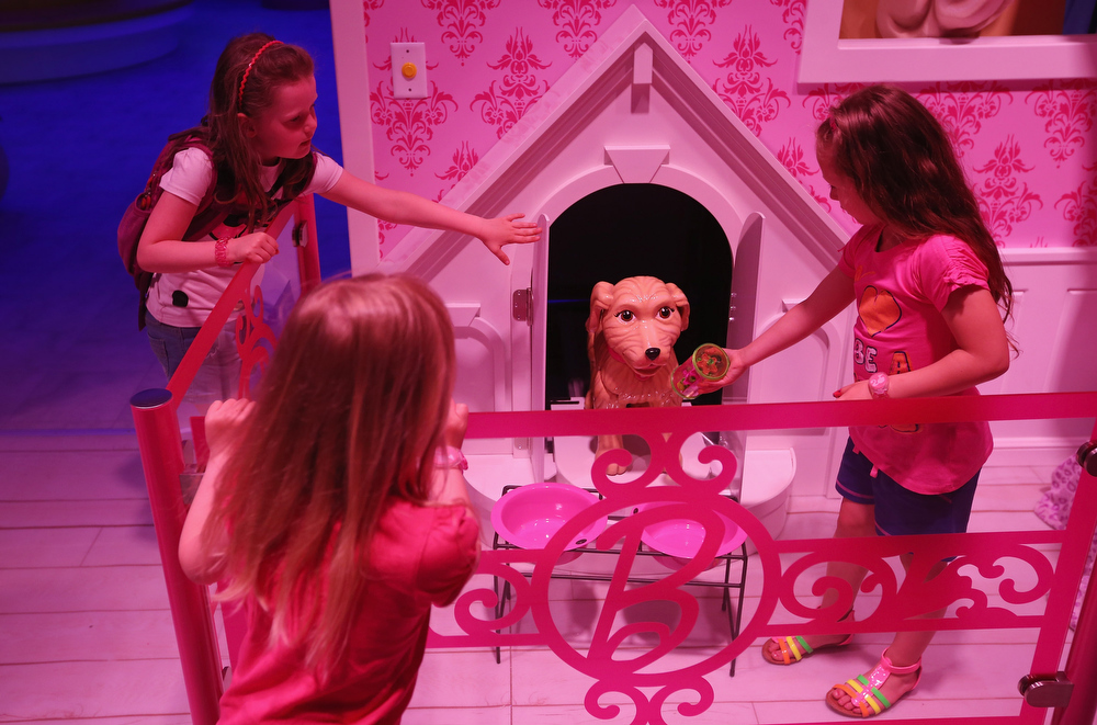 . Lara (L), Josi and Luna, all 6, pet a plastic dog that emerged from his doghouse at the Barbie Dreamhouse Experience on May 16, 2013 in Berlin, Germany. The Barbie Dreamhouse is a life-sized house full of Barbie fashion, furniture and accessories and will be open to the public until August 25 before it moves on to other cities in Europe.  (Photo by Sean Gallup/Getty Images)