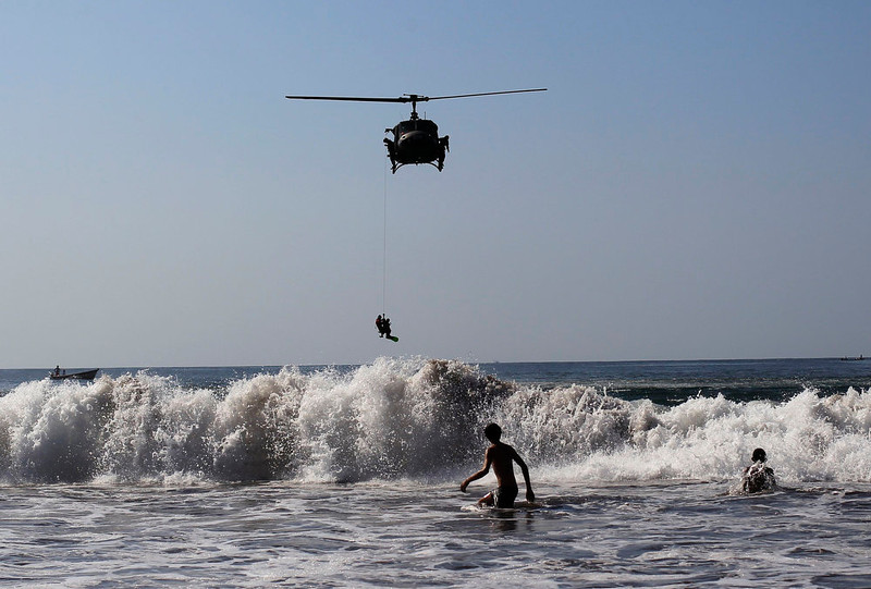 . The Air Force rescue team take part in a drill during the annual Paso del Hombre endurance challenge at La Libertad port in El Salvador February 24, 2013. About 370 male and female lifeguard volunteers swam for four to five hours continuously during the 49th edition of the event organized by the Salvadorian Red Cross in collaboration with the Navy, Coast Guard, Air Force and Civil National Police, local media reported. REUTERS/Ulises Rodriguez