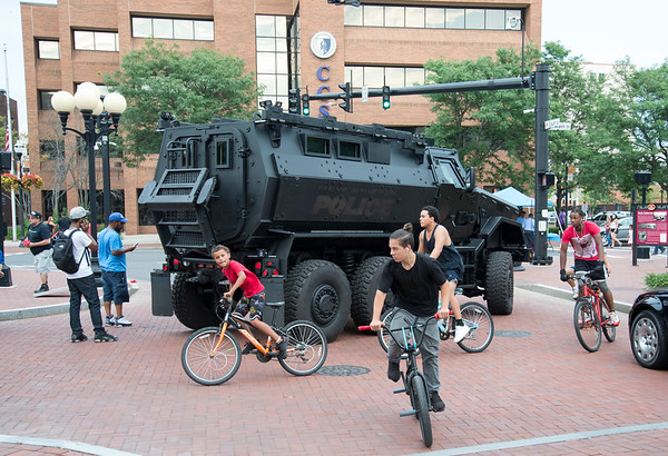 08/06/19 Wesley Bunnell | Staff The New Britain and CCSU Police held National Night out in Central Park on Tuesday evening as part of a nationwide night out designed to foster camaraderie between police and local communities. Kids ride their bikes past a police armored vehicle.