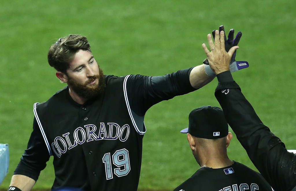 . LOS ANGELES, CA - APRIL 25: Charlie Blackmon #19 of the Colorado Rockies is greeted as he returns to the dugout after getting the go ahead RBI and then scoring a run in the 11th inning against the Los Angeles Dodgers at Dodger Stadium on April 25, 2014 in Los Angeles, California. The Rockies won 5-4 in 11 innings.  (Photo by Stephen Dunn/Getty Images)