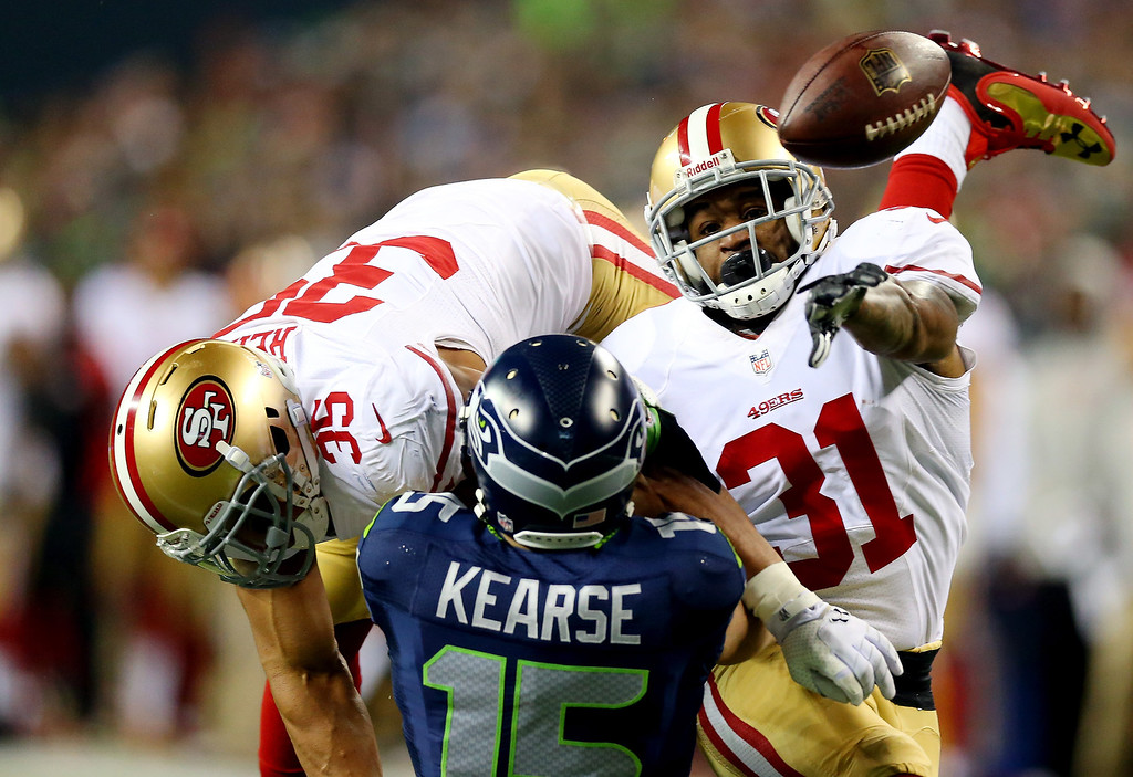 . Wide receiver Jermaine Kearse #15 of the Seattle Seahawks is hit by free safety Eric Reid #35 and strong safety Donte Whitner #31 of the San Francisco 49ers to break up the pass in the second half in the 2014 NFC Championship at CenturyLink Field on January 19, 2014 in Seattle, Washington.  (Photo by Ronald Martinez/Getty Images)