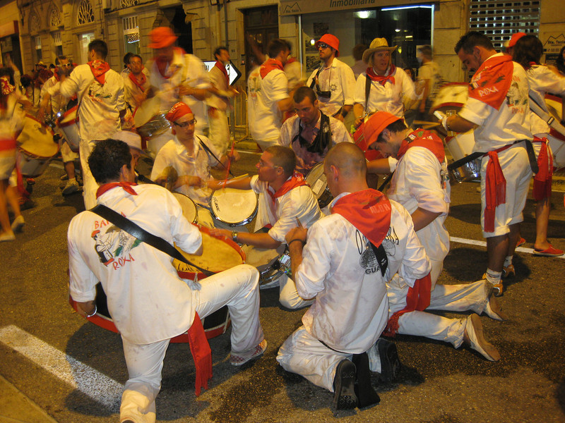 Men dressed in white with red kerchiefs and hats play at a drum party in Galicia, Spain.
