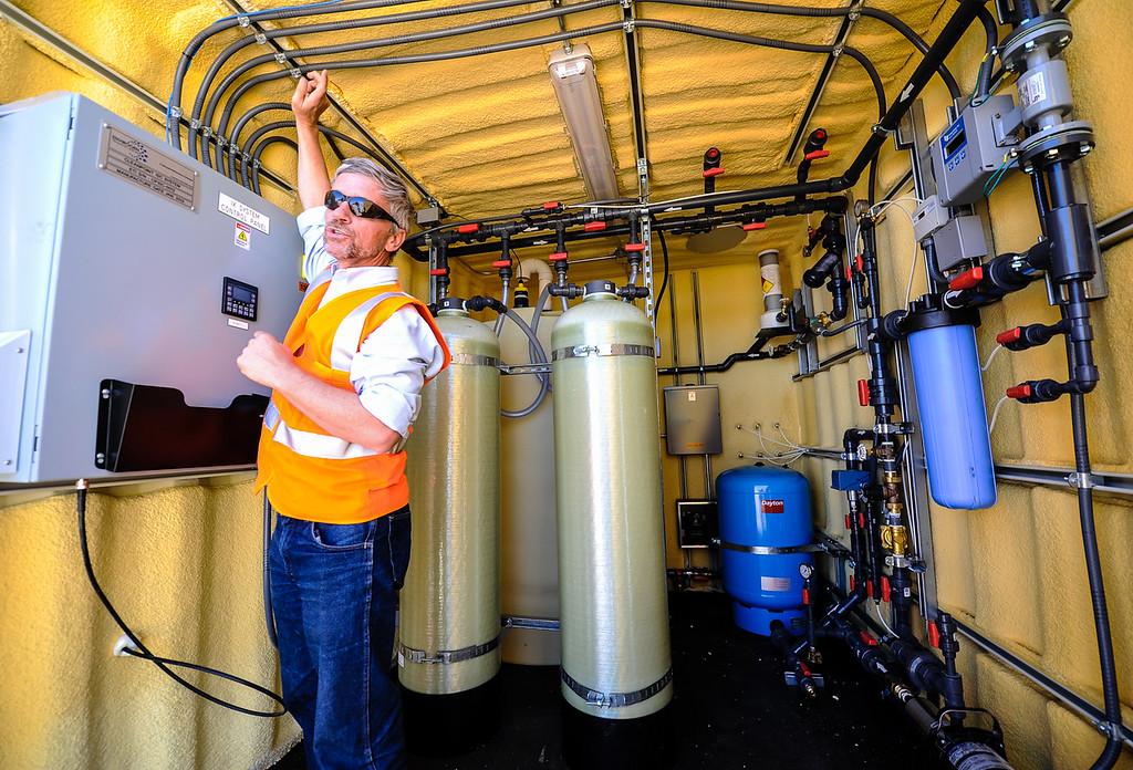 . PG&E Environmental Engineer Kevin Sullivan discusses the whole house water filtration process inside a unit in Hinkley, Calif. on Thursday, May 2, 2013. Sullivan leads the company\'s Hinkley remediation program. (Rachel Luna / San Bernardino Sun)
