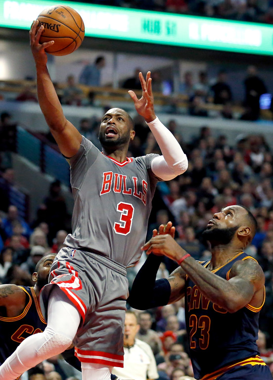 . Chicago Bulls guard Dwyane Wade, left, drives to the basket as Cleveland Cavaliers forward LeBron James watches during the second half of an NBA basketball game Friday, Dec. 2, 2016, in Chicago. (AP Photo/Nam Y. Huh)