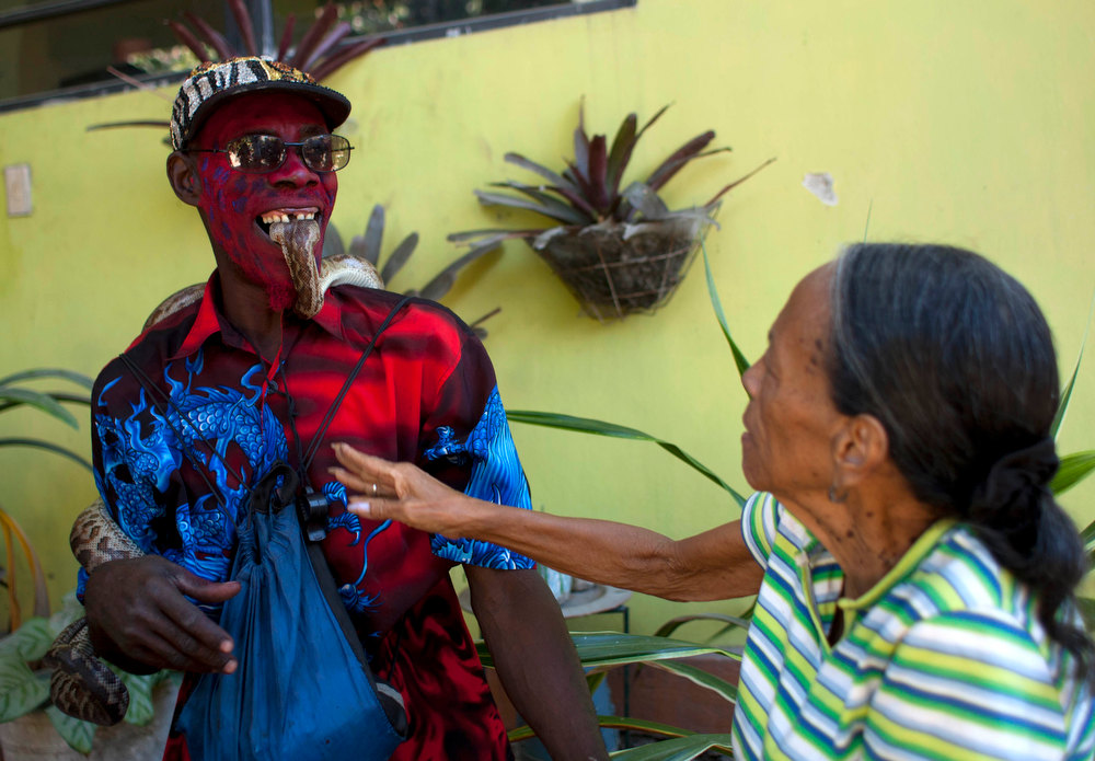 . In this Jan. 27, 2013 photo, snake handler Saintilus Resilus holds a snake with his teeth as he performs for money during the pre-Lenten Carnival season, near his home in Petionville, Haiti. Resilus has used snakes and other animals to earn a little money since at least 1974. (AP Photo/Dieu Nalio Chery)