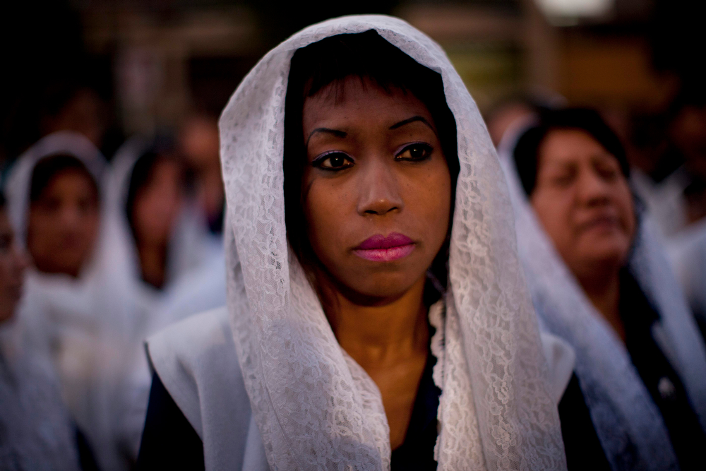 ". A woman waits for the star of a Good Friday procession honoring ""The Lord of Miracles\"", the patron saint of Lima, Peru, on Friday, April 18, 2014. Christians all over the world are marking Good Friday, the day when Jesus Christ was crucified. (AP Photo/Rodrigo Abd)"